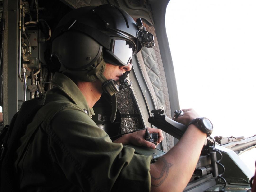 Un mitragliere sorveglia il territorio da un elicottero CH 47