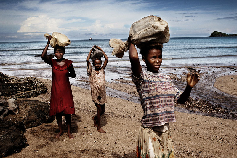Donne e bambine portano le pietre al villaggio