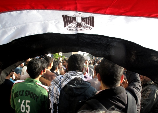 •La bandiera egiziana sventolata di fronte alla polizia