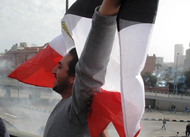 La bandiera egiziana sventolata di fronte alla polizia